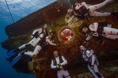 Aquanauts in dive suits pose for photo outside undersea habitat -  16-day NASA Extreme Environment Mission Operations (NEEMO) 21 expedition