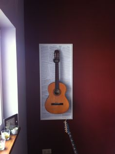 Guitar hanger. 1) cut a board to size needed; 2) screw it to wall; 3) print out music sheets; 4) randomly glue them to the board; 5) cut off the excess paper; 6) glue polystyrene coving as a frame of the borad 7) screw a guitar hanger to the board