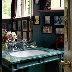 IN THE GREEN  A gorgeous malachite topped sink paired with bottle-green walls and black and white photographs is a winning combination in this house by designer and architect Robert Hardwick.