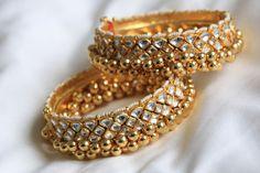 Ethnic jadtar kundan bangle with delicate pearl and gold ball hangings. It is adorned with real kundan polki and golden ghungroo beads. Kundan Bangles, Bridal Bangles, Bridal Jewelry, Gold Jewelry, Wedding Jewellery Inspiration, Indian Wedding Jewelry, Indian Bridal, Indian Jewelry, Antique Jewellery Designs