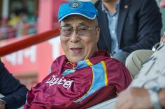 His Holiness the Dalai Lama wearing a West Indies cricket jersey signed by the members of the West Indies team and a cap from the India cricket team during his visit to the HPCA Stadium in Dharamsala, India to greet the team members before the one-day international match between India and West Indies on October 17, 2014. (Photo by Tenzin Choejor/OHHDL)