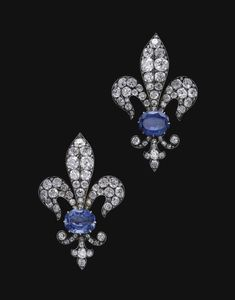 PAIR OF SAPPHIRE AND DIAMOND BROOCHES, LATE 19TH CENTURY. Each designed as a fleur de lys set with cushion-shaped, circular-, single-cut and rose diamonds, set at the centre with a modified octagonal-shaped sapphire, detachable brooch fitting later added.