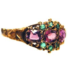 Lovely Victorian multistone cluster ring set with amethysts and emeralds in an elaborate 12K yellow gold setting. The ring has hallmarks for Birmingham, England, 1870.