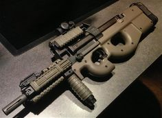 Custom PS90Civilian model of the FN P90, the PS90 has an extended barrel to maintain non-SBR status. There are several aftermarket options that will cover up the exposed barrel; in many cases it's a quad rail that can be used to add lights, lasers, forward grips etc. Note the Manta Defense Rail Guards which have special pockets that allow for inserting your light or laser wire, along with pressure switches for a very clean look. (GRH)
