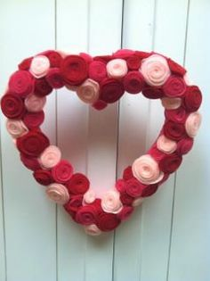 heart shaped wreath covered in fabric and felt flower rosettes.