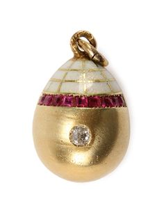RUSSIAN GOLD, ENAMELED AND DIAMOND SET EASTER EGG PENDANT, MOSCOW, 1908-1917. The top portion of egg in white enamel with gold net overlay, banded with cut inset rubies, and at center a rose cut diamond. Hallmarked Moscow 1908-1917, indistinguishable makers mark, and 56 gold standard (14K).