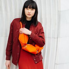 Shaped like a fortune cookie, this handbag offers two compartments for neatly organizing your belongings, with each compartment being large enough to store everyday objects such as a phone, wallet or eyewear case. Made from bright red 100% Polyester with a silky feel, the TARA M sits neatly at hip height, for easy-access to your essentials. Tara M, Red Handbag, Fortune Cookie, Everyday Objects, Phone Wallet, Easy Access, Eyewear, Organizing, Essentials