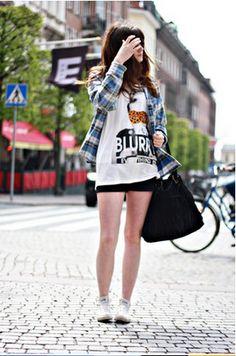 Um look bem street, com camisa xadrez azul, preta e branca; camiseta grande com estampa, shortinho preto, tênis e maxi bolsa. Ela misturou super bem muitas peças-tendência!
