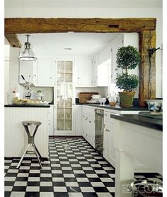 Wood beam, black and white floor, white cabinets