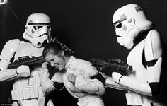 Carrie Fisher as Princess Leia having a fit of the giggles surrounding by two fearsome Stormtroopers