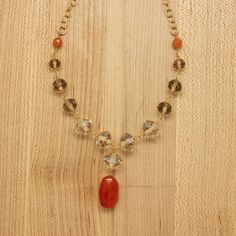 Carnelian and glass crystal wire wrap necklace. Gold plate over brass chain, measuring 18″ with a 2″ extender chain. Handmade in Portland, Oregon.
