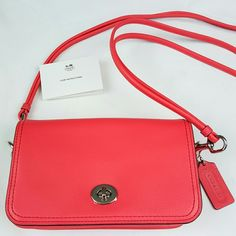 COACH Legacy Penny Crossbody Bag in Pink This is a gorgeous, authentic Coach purse (style 19914). It has never been used (it still has protective film over the metal closure!). The exterior of the purse is a pink-salmon color, while the interior is beige with pink trim. Original Coach care instructions included. Coach Bags Crossbody Bags