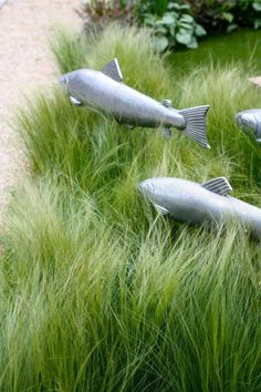 Fish sculptures for the garden; put them in a patch of ornamental grass