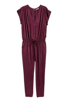 H&M+ Combi-pantalon: Combinaison en viscose tissée à manches courtes. Modèle avec encolure en V et fronces au niveau des épaules. Fermeture par agrafe dans le dos ouvert. Découpe à la taille avec mince élastique et lien de serrage. Poches latérales et jambes effilées. Non doublée.