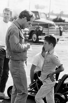 Paul Newman signing an autograph for a young fan.