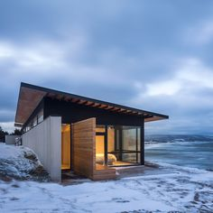 Omar Gandhi Architect created a vacation home in Nova Scotia for an urban couple, with floor-to-ceiling windows that provide sweeping views of the sea.