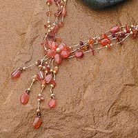 Looks like silk cord knotted around stones, pearls, and crystals in this piece.