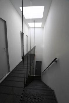 http://www.yvesdeneyer.be/metal.htm  Ensemble de 2 escaliers et 2 passerelles. Structure en acier plat et barres de diam 12mm. Toute la structure est soutenue par 3 barres de diam. 12mm fixées au-dessus du faux-plafond, par ancrages chimiques. Planchers et marches en tôle perforée R10T15 d'épaisseur 3mm. Les barres servent également de garde-corps. Peinture polyuréthane 2 composants gris foncé mat métallisé, appliquée sur chantier.