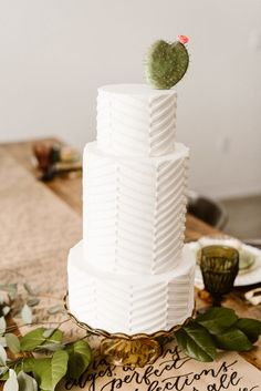 Modern geometric patterned wedding cake with cactus leaf topper | Image by Carrie J Photography