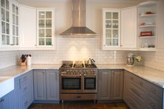 """Ikea Lidingo Gray lower cabinets with Lidingo white upper cabinets. Marble countertops. Verona 36"""" stainless dual fuel range with double oven. Subway tile backsplash. Indian Autumn Slate floor."""