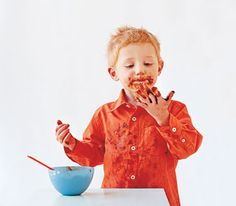 Messy little red-headed boy with pasta sauce all over his face