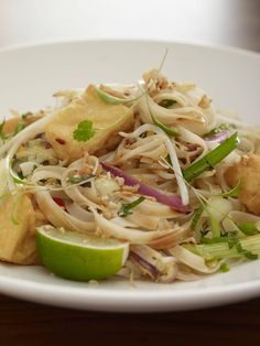 egg-fried rice noodles in a tamarind sauce with fried tofu, beansprouts, leeks, chinese chives, spring onions, garlic, ginger, mint and chillies. garnished with coriander cress, fried shallots, peanuts and lime