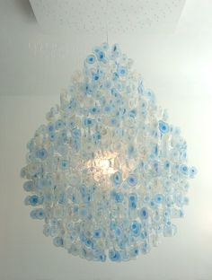 Plastic Water Bottle Bottoms Chandelier - Designer Stuart Haygarth creates chandeliers using the bottoms of plastic water bottles. Showing at Design Miami, Haygarth says his creations focus 'on the overlooked sculptural beauty of these plastic water containers.' the unused part can be used in the garden or as funnels. Via Dezeen.