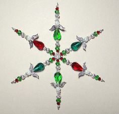 Beaded Snowflake Ornament ~ Angel Suncatcher ~ Green & Red Angel Christmas Ornament ~ Crystal Sun Catcher ~ Christmas Winter Decor  This beautiful guardian angel ornament ~ sun catcher is handcrafted using light siam, grass green and emerald faceted crystal beads, white glass pearls and silver plated angel wings, halo and accent beads. Comes with a red satin ribbon for hanging and cotton filled kraft box for gift giving and storage. Beautiful traditional Christmas colors!  Can be used as a…