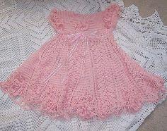 """Magnifique robe rose pour fillette , ornées de fleurs , trouvée sur la page facebook de """" Crochet Comparido """" , avec ses grilles gratuites ."""