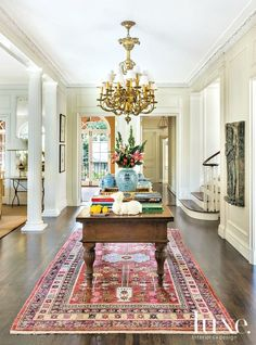 Spring style!! Wonderful table and flowers and books and pink rug in a large sunny light foyer, front hallway, entry!