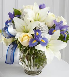 Christmas & Holiday Flowers - Miracle Light Hanukkah Bouquet - DELUXE - Celebrate this miraculous and meaningful holiday with an abundance of beautiful blooms. Blue iris creates a splash of color against a backdrop of white roses and white Asiatic lilies accented with lush greens, silver pinecones and blue and silver organza ribbon, gorgeously situated in a clear glass ginger jar vase.