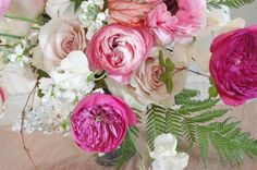 Bright Summer Arrangement in a giant shell: ANGEL WINGED BEGONIA LEAVES, BOSTON IVY, CONCH SHELL, DARCY ROSES, FERNS, FRENCH RANUNCULUS, FUSCHIA PEONIES, GLORIOSA LILIES, GRASSES, SHELL ARRNAGEMENT, SILVER DOLLARS, STOCK, SWEET PEAS