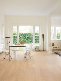 Quick-Step Laminate Flooring - Eligna Wide 'Oak white oiled' (UW1538) in a modern dining room. To find more dining room inspiration, visit our website: https://www.quick-step.co.uk/en-gb/room-types/choose-the-perfect-dining-room-flooring #salleamanger #eetkamer