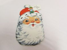 """Santa Christmas Card.  This is a vintage Gibson greeting card.  It features Santa's jolly face with an elf sitting on his hat.  The inscription reads Just For You.  The card has been used.  It is approx. 6 1/4"""" x 3"""".  There is some wear and discolorations."""