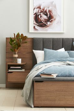 Modern luxe bedroom with grey panel upholstered bedhead, floral artwork and magnolia branches in vase