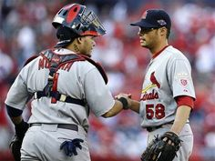 St. Louis Cardinals catcher Yadier Molina, left, and relief pitcher Joe Kelly shake hands after closing out Game 3 of the National League division baseball series against the Washington Nationals on Wednesday, Oct. 10, 2012, in Washington. St. Louis won 8-0.