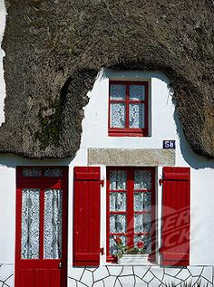 Exterior of a thatched cottage with red door and shutters in La Grande Briere, Ile de Fedrun, Pays de la Loire, France, Europe