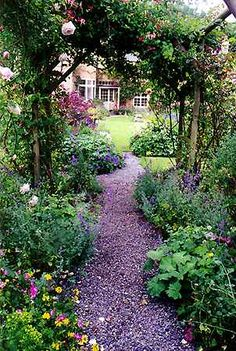 gravel path under a rose arbor