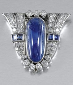 An Art Déco Sapphire and Diamond Clip Brooch, 1930. The shield-shaped plaque, set to the centre with an oval cabochon sapphire, to tapered shoulders millegrain-set with step-cut sapphires, brilliant- and single-cut diamonds, fitted case.