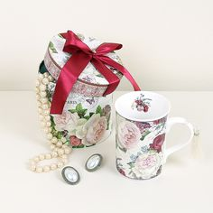 An ideal gift to remind someone that you are thinking of them. This beautiful mug made from high quality porcelain, has been adorned with blush pink camellias, hydrangeas, roses amongst other flowers and it will hold a generous portion of tea, coffee or even a hot chocolate! To the inside of the mug, there is a small floral print which clearly shows the thoughtfulness of the design process. This will arrive with a pretty cream detachable tassel on the handle which adds a real touch of…