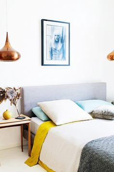 Yellow, blue, and grey bedroom with copper light fixtures.