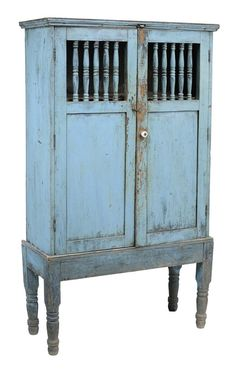 Spanish Colonial Blue-Painted Cabinet. probably Mexican, late 19th century, pine throughout with two spindled and paneled doors opening to shelved interior, early blue paint, dovetailed construction, sits on separate frame of through-tenon construction, 59 x 35 x 13-1/2 in. Provenance: Dewey Galleries, Santa Fe, New Mexico; Kania Ferrin Gallery; Estate of the Late Nancy Webb, Tryon, North Carolina