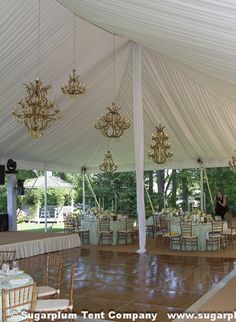 I love the look of liners and leg drapes underneath the tent. The gold chandeliers are eye-catching against the immaculate white!