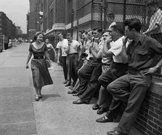 A girl smiles as classmates wolf-whistle at her as she arrives at school. NYC, 1959.