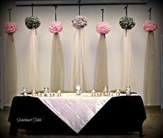 Floating pompoms with tulle draping made an unique, beautiful, & economical backdrop for a head reception table.