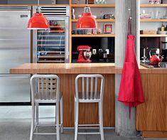 Na cozinha gourmet, um dos pilotis é envolvido pela bancada do ambiente. Detalhes em vermelho quebram (Foto: Denilson Machado/Editora Globo)