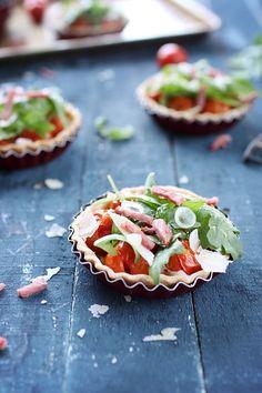 Ces tartelettes aux tomates cerises font une jolie entrée estivale, à servir à température ambiante ou bien froides. Elles sont accompagnées de bacon, d'oi