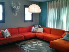 Living room complete w giant orange couch, cardboard deer and perfect hue blue wall