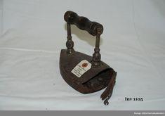 Strykjärn från år 1727 järn, med lod. Strykjäret är elegant utförd med svarvat svart trähandtag. Strykjärnets bakstycke öppnas med hjälp av en vackert smidd låslinka.   fr. Vassunda sn. Uppland