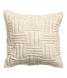 Pattern-knit cushion cover with wool content. Woven cotton back and concealed zip.